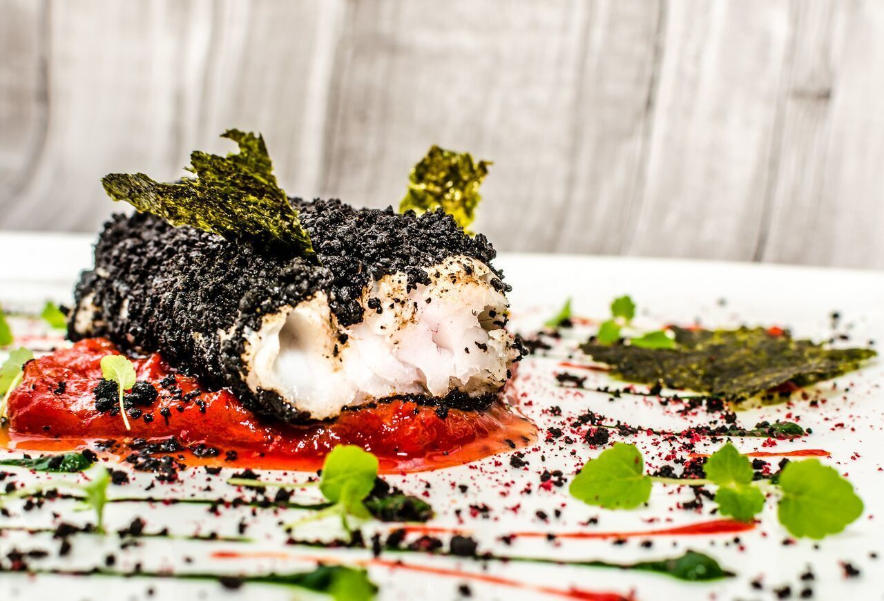 Cod 'bourdeto' in dark olive crust and nori leaves